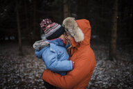 Happy mother carrying daughter while standing in forest during winter - CAVF58349