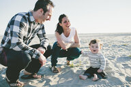 Portrait of cheerful son with parents sitting on sand at beach - CAVF58367