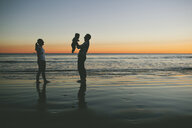 Woman looking at man carrying son at beach during sunset - CAVF58376