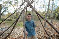 Portrait of boy standing amidst wood at park - CAVF58382