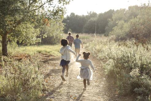 Rear view of siblings running on field at park - CAVF58385