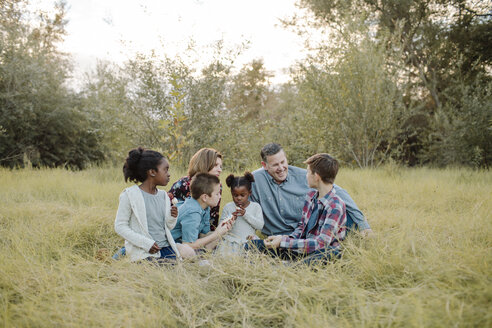 Family sitting on grassy field at park during picnic - CAVF58397