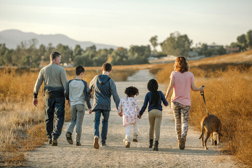 Rear view of family with dog walking on dirt road against sky at forest - CAVF58409