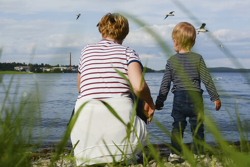 Finland, Kuopio, back view of mother and little daughter watching seagulls at lakeshore - PSIF00171