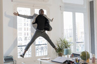 Happy young businessman jumping in the air in his office - GRSF00025