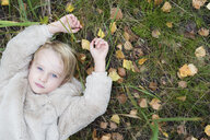 Portrait of blond girl lying on a meadow in autumn, top view - PSIF00185