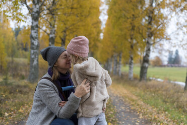 Mother and little daughter cuddling outdoors in autumn - PSIF00188