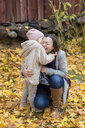 Finland, Kuopio, mother and little daughter cuddling together in autumn - PSIF00191