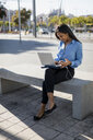 Businesswoman using laptop, holding smartphone - MAUF01829