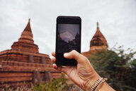Cropped hand of man photographing Buddhist temple against sky - CAVF58430