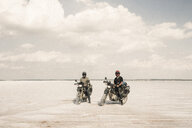 Portrait of friends sitting on motorbikes at desert road against cloudy sky - CAVF58439