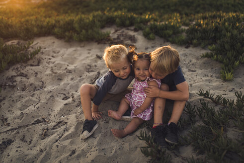 High angle view of siblings sitting on sand at beach during sunset - CAVF58460