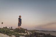 Full length of boy standing on sand at beach against sky during sunset - CAVF58463