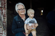 Grandmother with grandson sitting at barn - CAVF58493