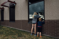 Rear view of siblings peeking through window while standing at backyard - CAVF58496