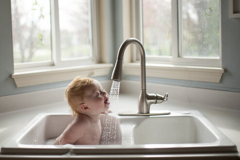 Cute baby boy sticking out tongue under running water from faucet in kitchen sink - CAVF58517