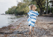 Rear view of girl wrapped in towel walking at lakeshore - CAVF58550
