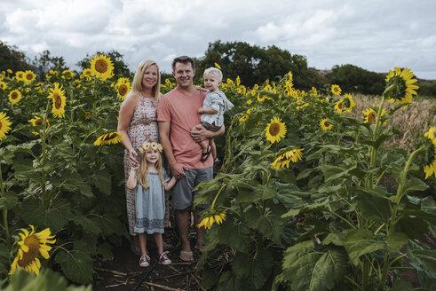 Full length portrait of smiling family standing amidst sunflowers - CAVF58583