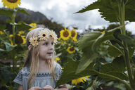 Close-up of girl looking away while standing amidst sunflowers - CAVF58586