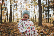 Cute girl with eyes closed laughing while standing at forest - CAVF58715