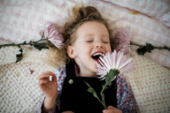 Overhead view of cheerful girl with gerbera lying on bed at home - CAVF58718