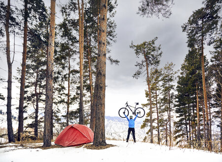 Rear view of man carrying bicycle while standing on snow covered mountain against sky at campsite - CAVF58733