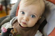 Close-up portrait of cute baby boy sitting on high chair at home - CAVF58757