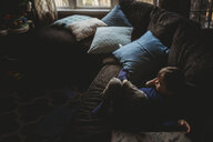High angle view of thoughtful boy looking away while relaxing on sofa at home - CAVF58769