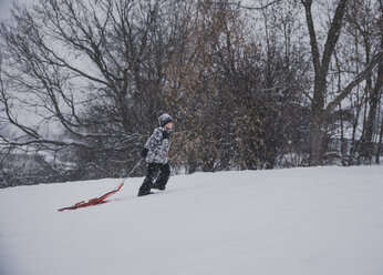 Side view of boy pulling sled while walking on snowy field against bare trees - CAVF58775
