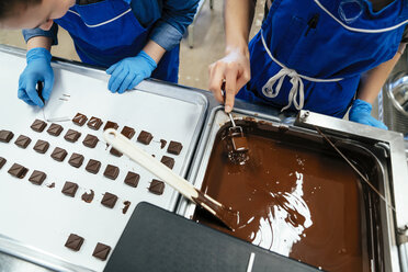 High angle view of coworkers preparing chocolates at factory - CAVF58802