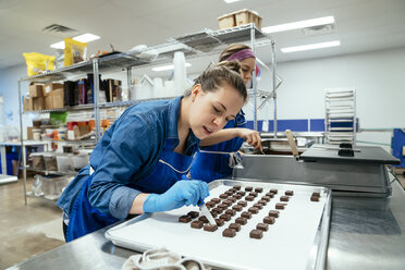 Female coworkers preparing chocolates at factory - CAVF58805
