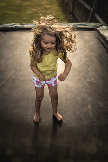 High angle view of playful girl standing on trampoline - CAVF58820