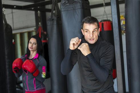 Coach training female boxer in gym - CAVF58835