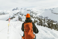 Rear view of hiker with backpack on snowcapped mountain during ski holiday - CAVF58877