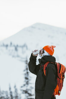 Side view of hiker with backpack having drink from can while standing against snowcapped mountain - CAVF58883