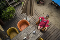 High angle view of woman with drink sitting at beach cafe - CAVF58889