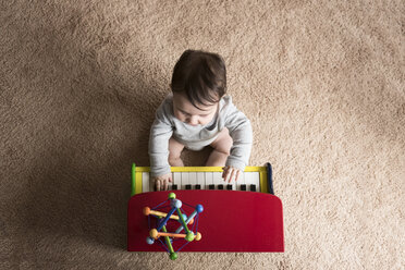 Overhead view of baby boy playing toy piano on carpet at home - CAVF58919