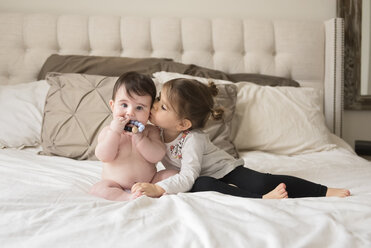 Loving sister kissing shirtless brother sitting on bed at home - CAVF58922