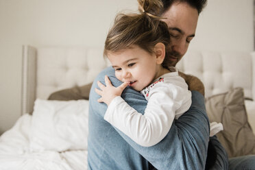 Loving father embracing daughter on bed at home - CAVF58925