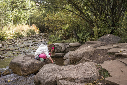 Side view of girl sitting on rock by river in forest - CAVF58982