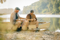 Friends talking while sitting by fishing rods on boat at lakeshore - CAVF59021