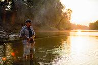 Senior man fishing while standing in lake during sunset - CAVF59054