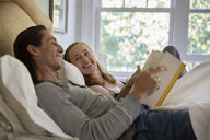Smiling couple on bed at home - CAVF59084