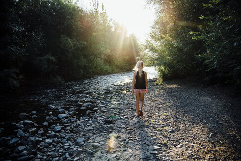 Rear view of carefree girl walking towards river in forest - CAVF59108