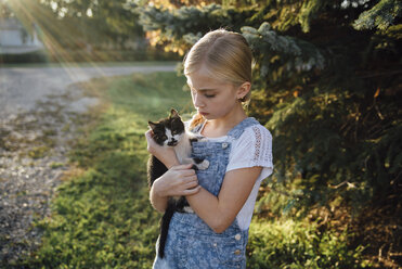Girl holding cat while standing on field - CAVF59114