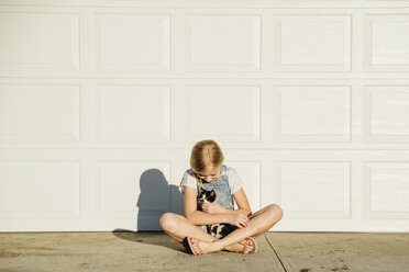 Full length of girl with cat sitting on footpath by wall during sunny day - CAVF59117
