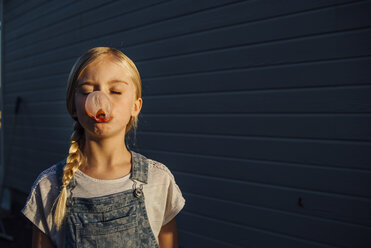 Girl with eyes closed blowing bubble gum while standing by wall - CAVF59120
