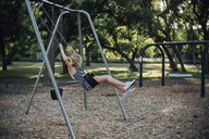 Side view of girl swinging at park - CAVF59132