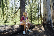 Portrait of girl sitting on log in forest - CAVF59141