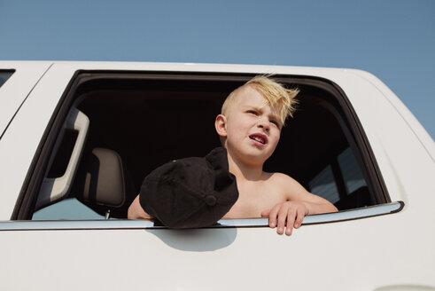 Low angle view of boy looking through window while sitting in vehicle against clear sky - CAVF59162